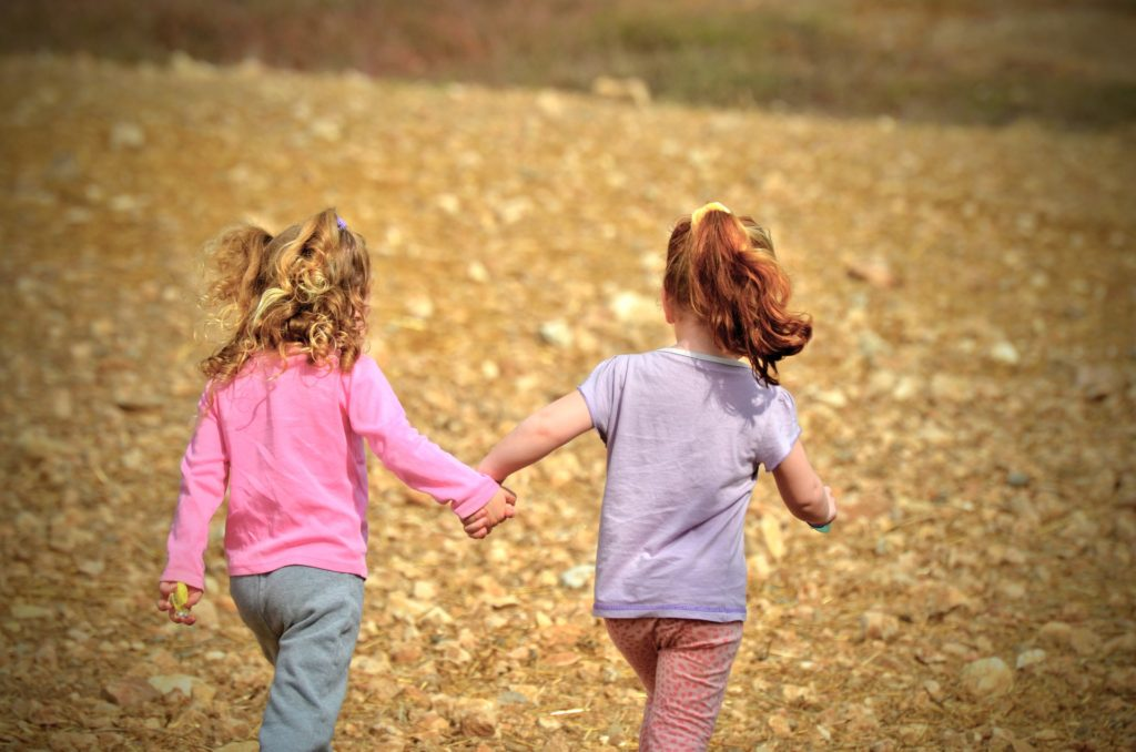 Two young girls holding hands while walking away from the camera