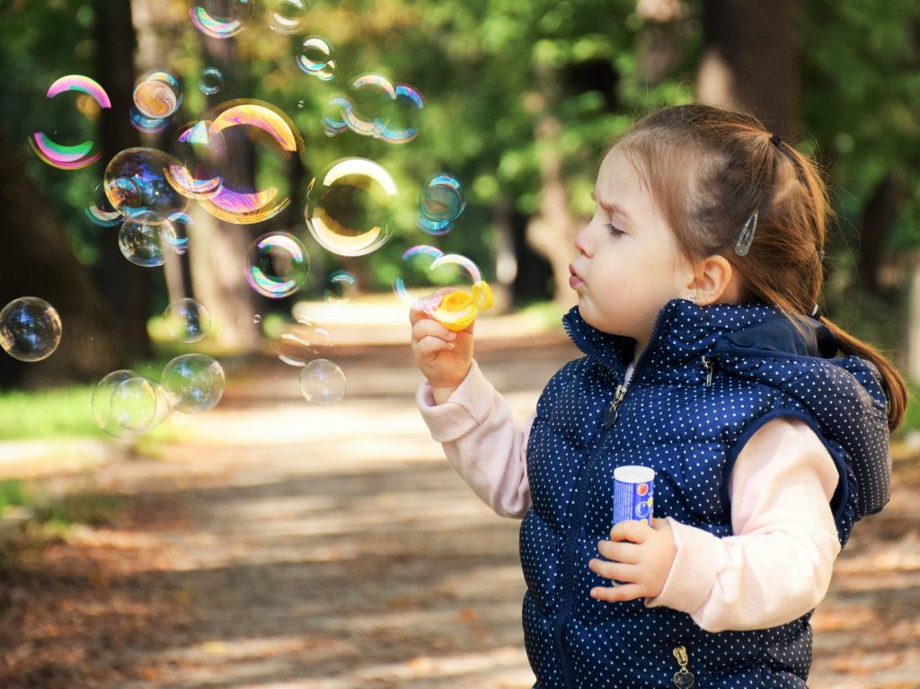 A toddler girl blowing bubbles outside