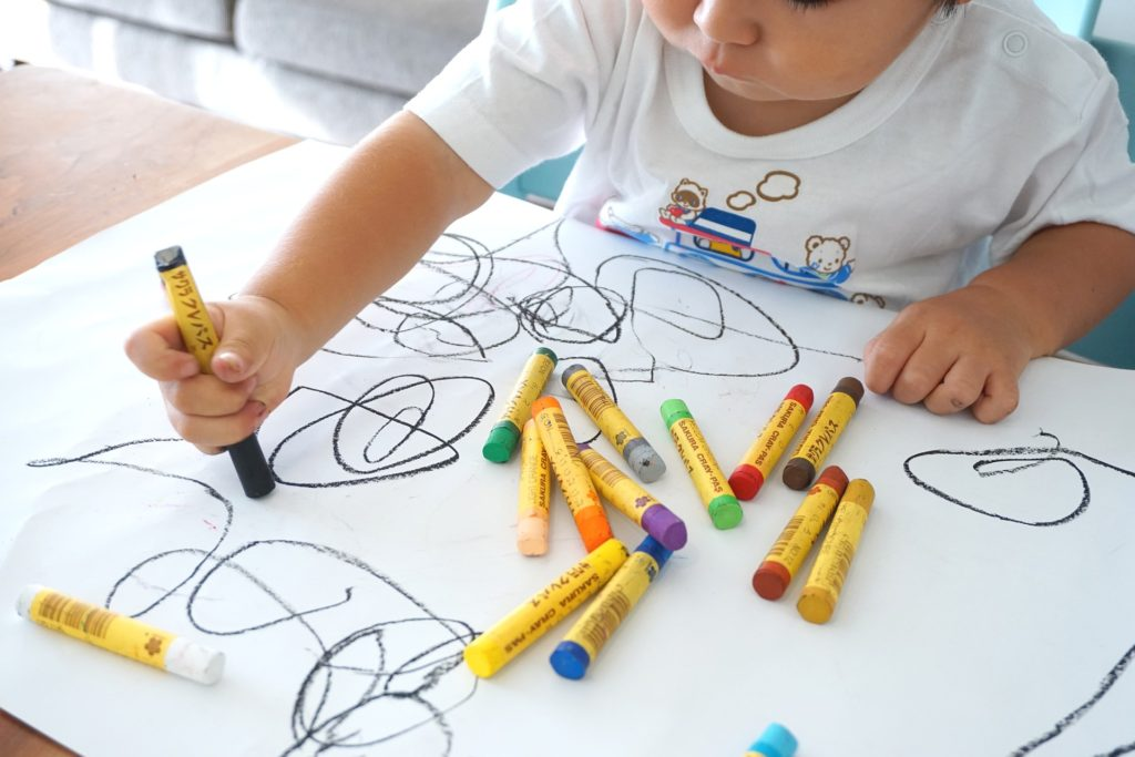 toddler drawing with crayons on a piece of paper