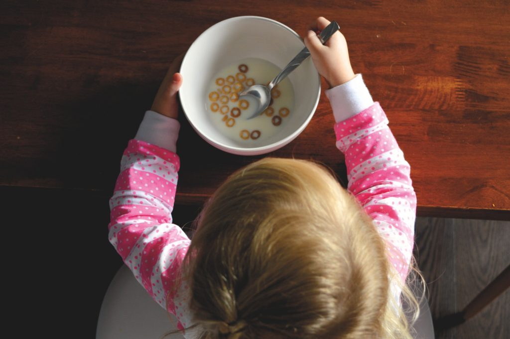 The top of a young girl's head as she sits in front of a bowl of cheerios and milk