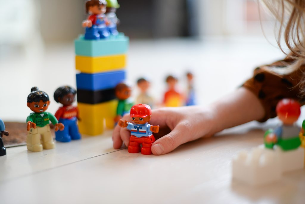 A child's hand playing with lego people and a tower of lego blocks