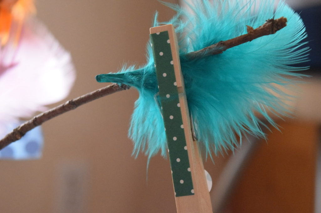 feather attached to stick with clothespin