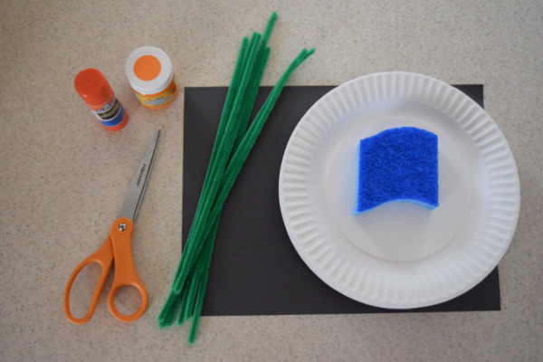 Supplies for easy pumpkin plate craft for toddlers - scissors, construction paper, paper plate, sponge, green pipe cleaners, orange paint, and glue stick.