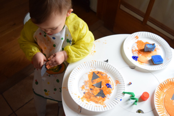 Toddler making pumpkin plate craft and using black construction paper.