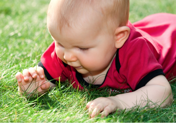 Baby lying ooutside on the grass on his belly