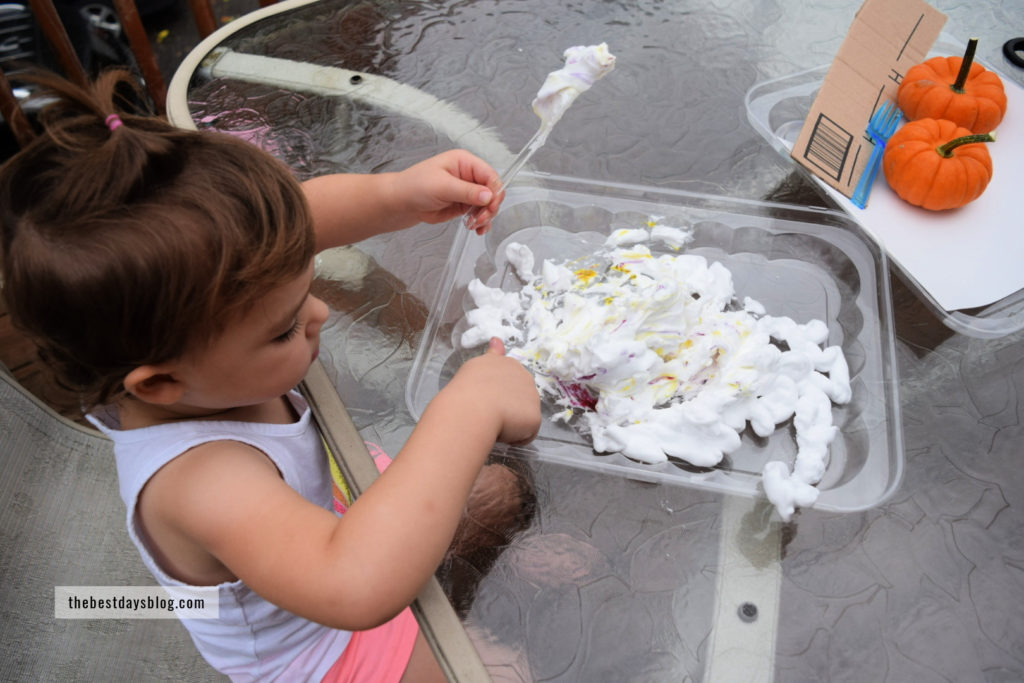 Preschool aged girl mixing food coloring and shaving cream together to make marbled paper