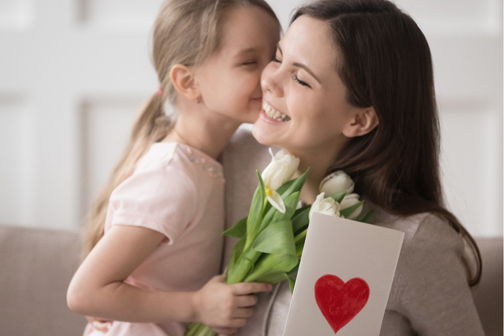 Young girl expressing thankfulness to woman with card and flowers
