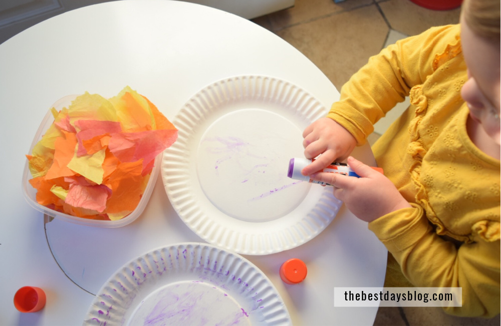 Toddler using gluestick to attach tissue paper to paper plate for turkey craft