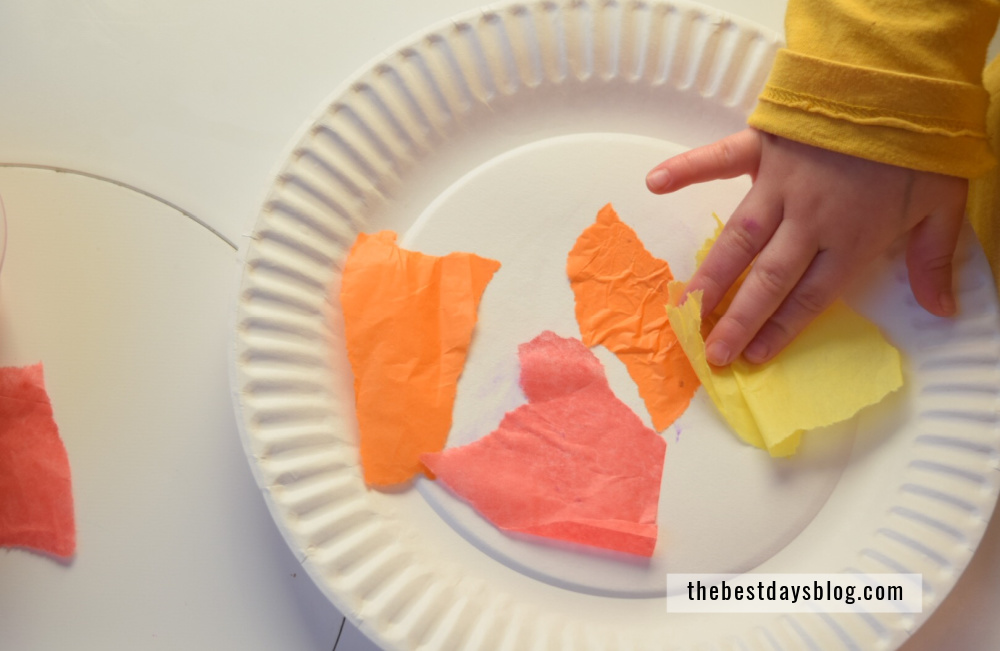 Toddler hand gluing tissue paper on to paper plate for turkey craft