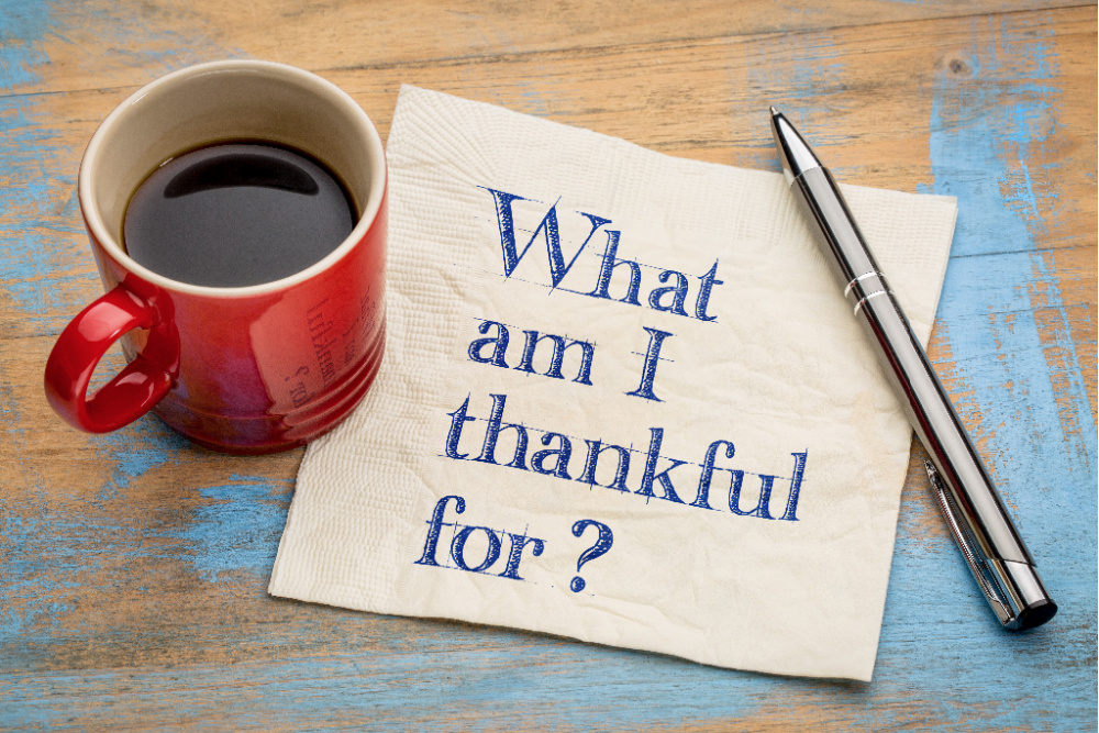 A cup of coffee and a pen with a note that says: what am I thankful for?