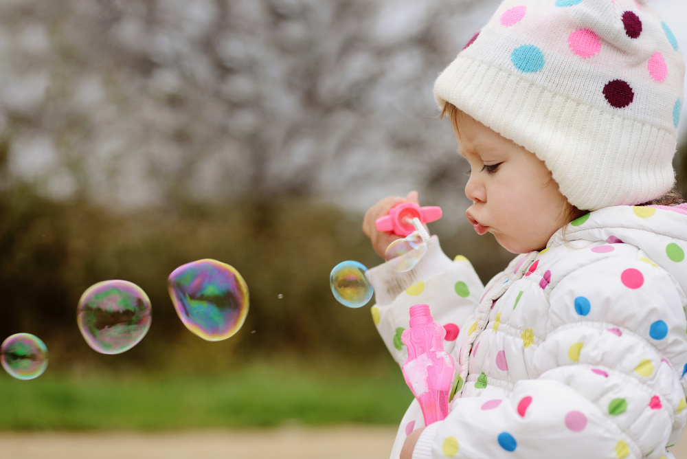 Toddler blowing bubbles outside. You can use bubbles to help your toddler learn to talk!