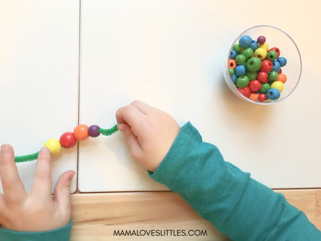 Toddler's hands stringing wooden beads onto pipe cleaners to make rainbows for St. Patrick's Day sensory bin