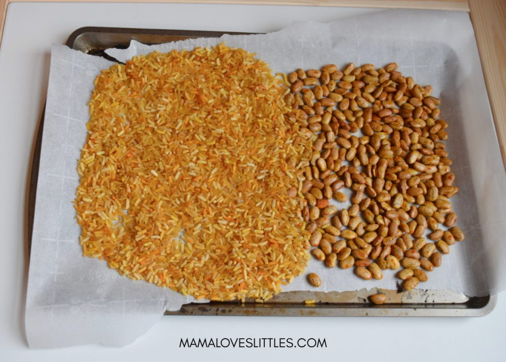 Rice and beans that have been dyed yellow for Pots of Gold sensory play are drying on a baking sheet with parchment paper