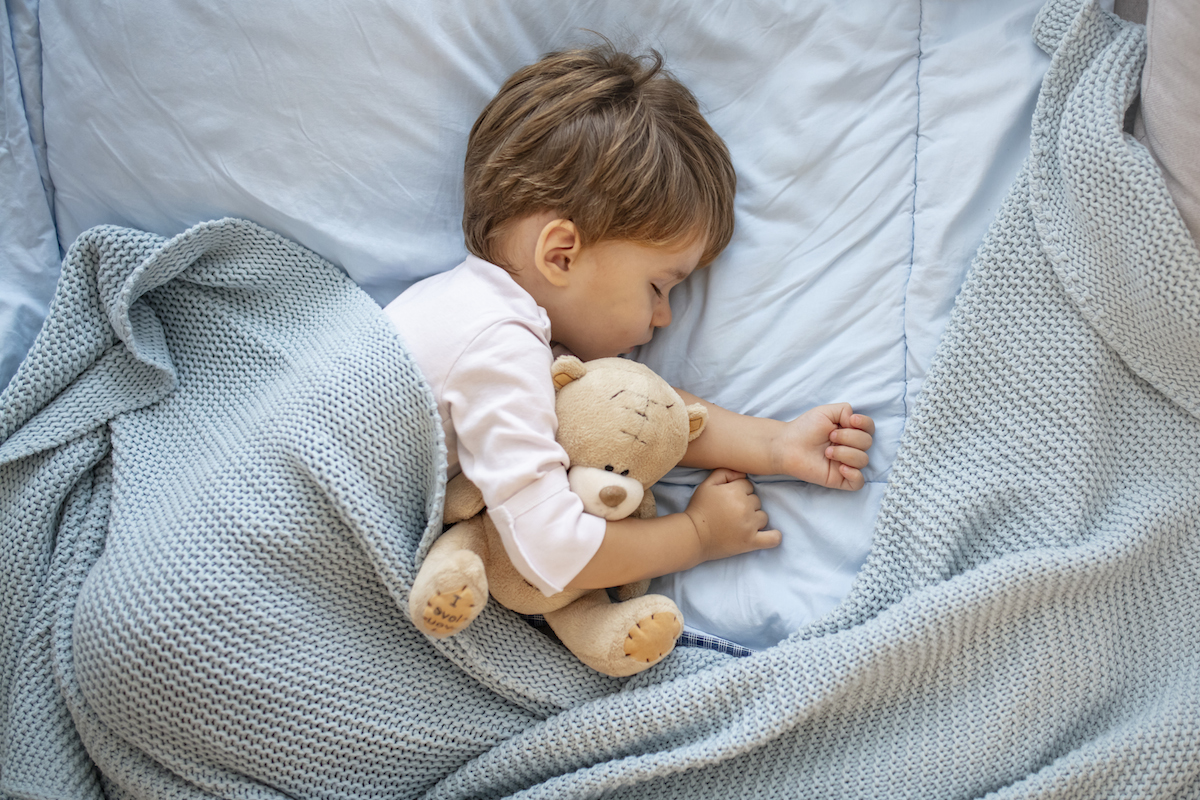 Toddler boy sleeping in bed with a teddy bear