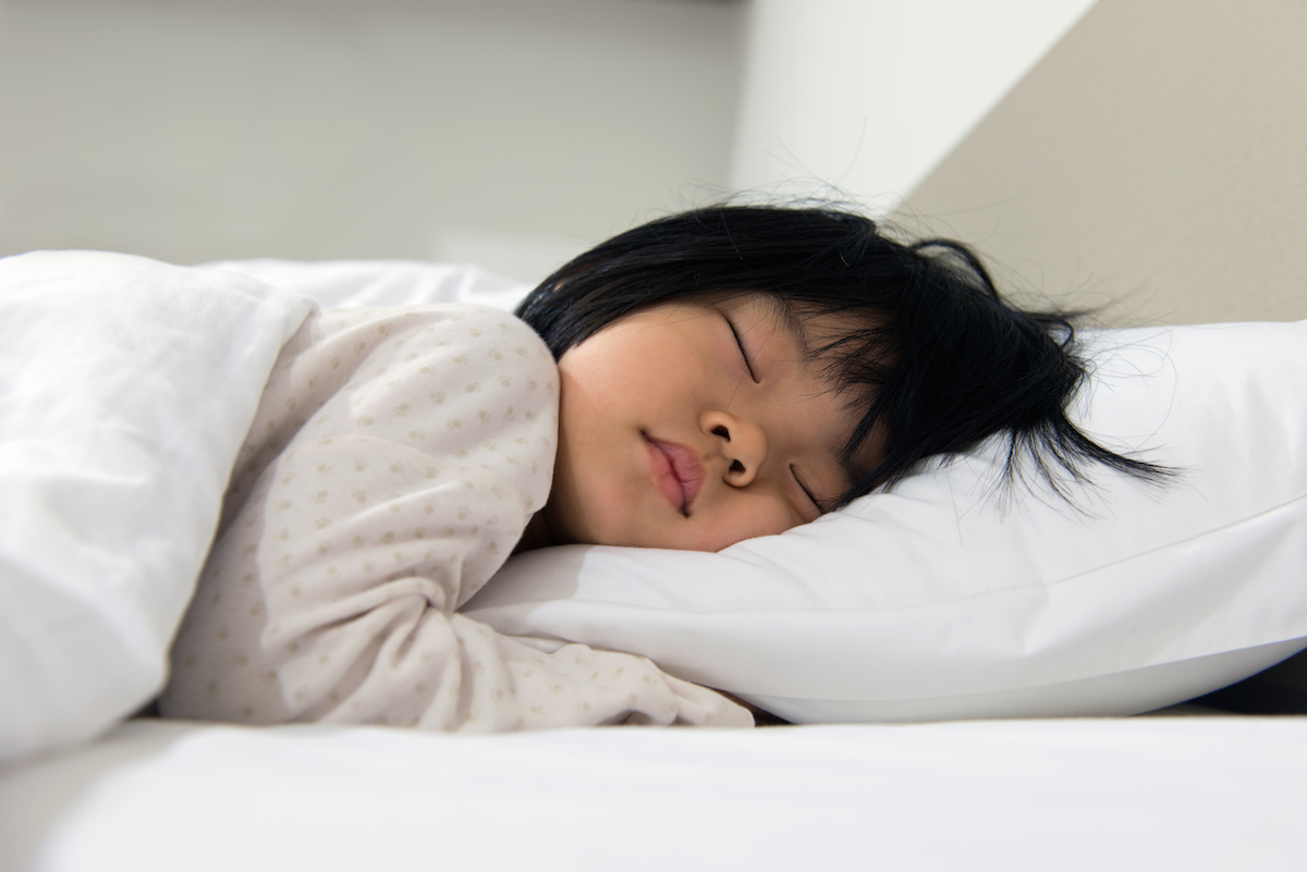 Toddler sleeping peacefully in a bed