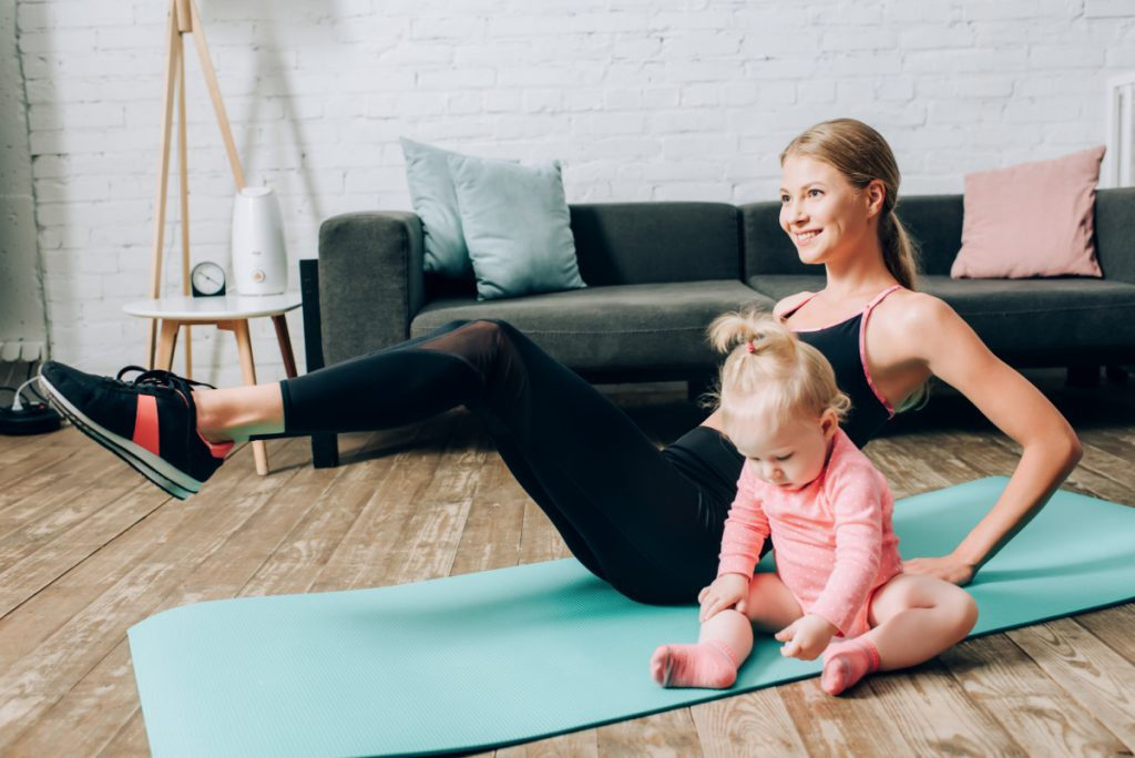 Mom exercising with toddler on yoga mat in living room