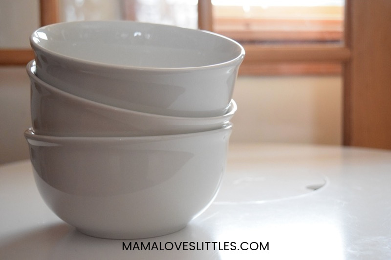 stack of white ceramic bowls on top of a table