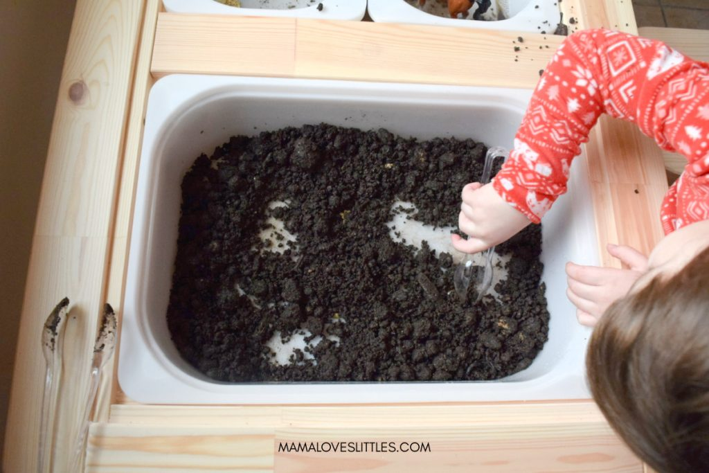 Little girl using tongs to find gold in dirt for sensory bin activity