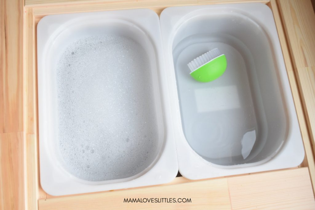 Two bins for Find the Gold St. Patrick's Day activity. One with soapy water and one with plain water with a green scrub brush.