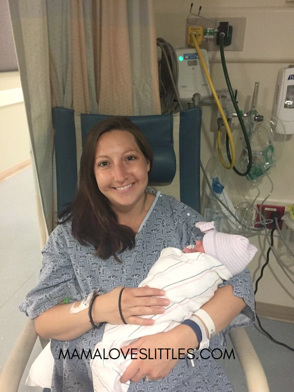 Woman sitting in chair and holding baby in hospital after giving birth