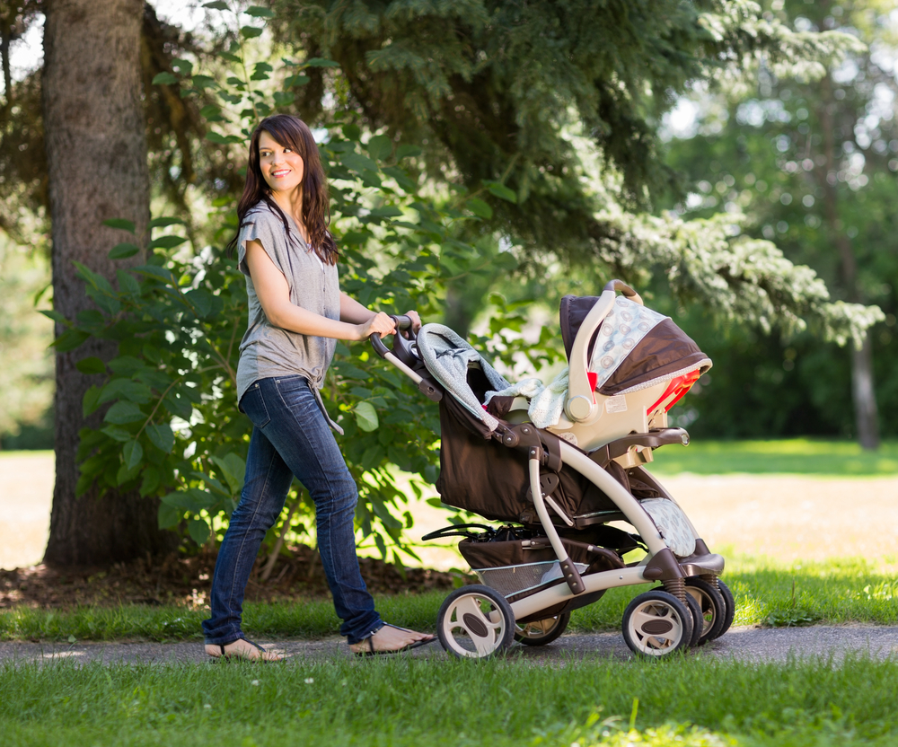 Woman pushing a stroller while taking a walk outside