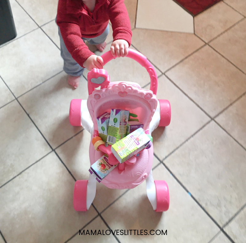 One year old boy pushing stroller filled with juice boxes