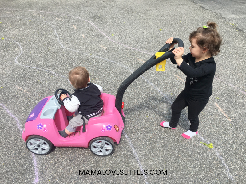 Little girl pushing one year old boy in toy car