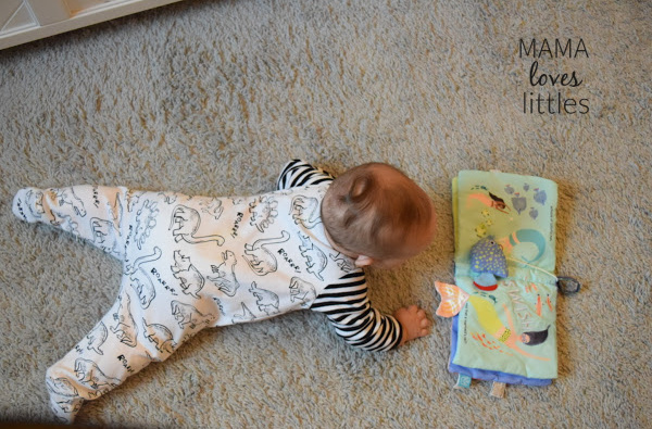 Baby lying on belly and playing with a soft book