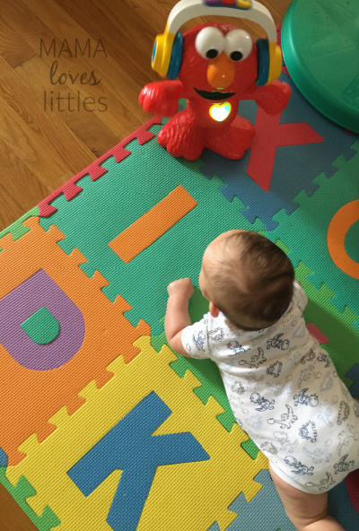 Baby watching dancing Elmo toy during tummy time