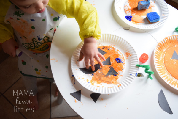 Toddler gluing a pumpkin mouth onto orange painted paper plate.