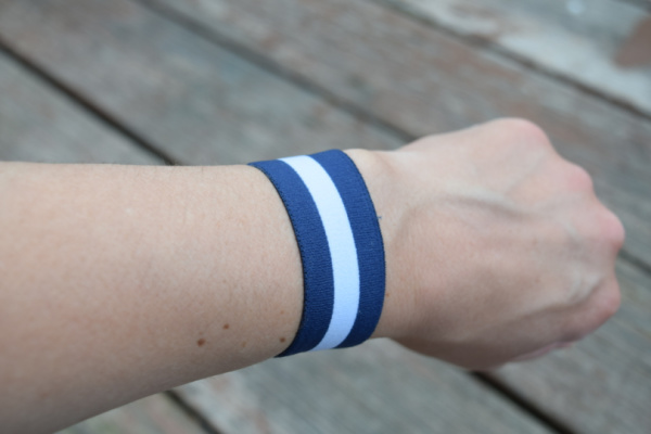 woman's arm with blue and white striped acupressure band for morning sickness
